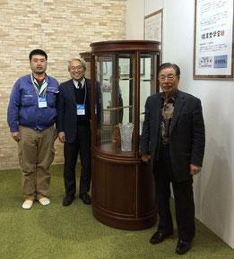 最先端のキュリオを制作した、左から横内真樹氏、小安専務理事、横内昭次郎理事長。