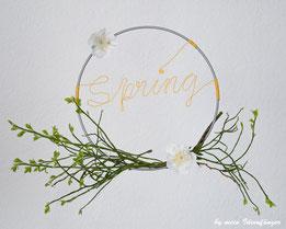 DIY Frühlingskranz aus einem Metallring, dem Schriftzug Spring aus Papierdraht und Blüten- sowie Pflanzenschmuck.