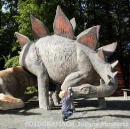 Kind spielt an Dinostatue