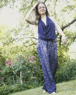 Dame mit Haremshose, Yogahose, Pluderhose (Pfauenfeder Muster, blau, Fairtrade) entspannt im Garten