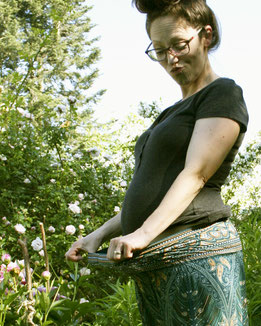 Schwangere Dame mit Umstandshose, Haremshose, Yogahose, Pluderhose mit Paisley- und Pfauenfeder-Muster, Fairtrade, glücklich im Garten
