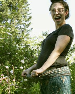 Schwangere Dame mit Umstandshose, Haremshose, Yogahose, Pluderhose mit Paisley- und Pfauenfeder-Muster, Fairtrade, entspannt im Garten