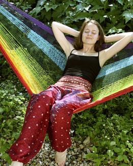 Dame mit Haremshose, Yogahose, Pluderhose (Pfauenfeder Muster, pink, Fairtrade) entspannt in der Hängematte