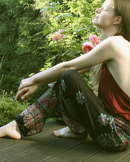 Frau entspannt im Garten mit Haremshose, Yogahose, Pluderhose für Damen, mit Mandala und Blumen Muster, schwarz / bunt, Fairtrade