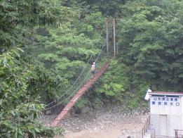 ▲朝日鉱泉登山口すぐの吊り橋を渡る田中さん