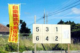 町内に設置された町長選のポスター掲示板と、近くでたなびく自衛隊誘致反対ののぼり。自衛隊配備の是非は最大の争点だが、両陣営の訴え方には相違がある(5日午後)