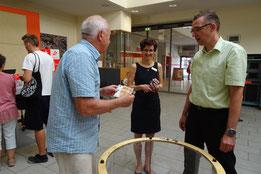 """V.l.n.r. : Herr Zitzmann vom Kirchbauverein zeigt Frau Eckardt und Herrn Hinsenbrock eine """"Großspende"""" aus dem Spendentrichter"""