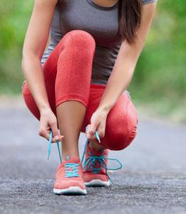 Sportlerin, die sich Laufschuhe anzieht