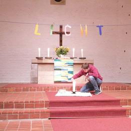 Zum Gebet zündeten alle am Altar ein Licht an.