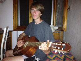 Junge Mann mit Gitarre kleine Wohnung Urlaub Reisen Backpacking Rucksack