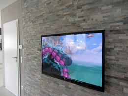 Unser Fernseher vor der Natursteinwand, die Kabel verlaufen wegen der besseren Optik innerhalb der Wand nach unten