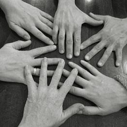 Hände einer Gruppe von vier Menschen auf einem Tisch -