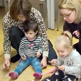 Mutter mit Kleinkind spielt Holzxylophon