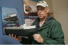 Kit Kartsen, manager of the Zeeland Historical Society, holds a model of the steamer Chicora, which shipwreck hunters are still searching for. Brian Forde.