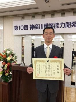 表彰状を手に、笑顔の三富啓成氏。