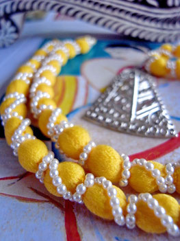 Indian, handcrafted, sterling-silver, filigree pendant on thick, canary-yellow, cotton/silk necklace, wrapped in small, ivory-coloured, Japanese pearls.