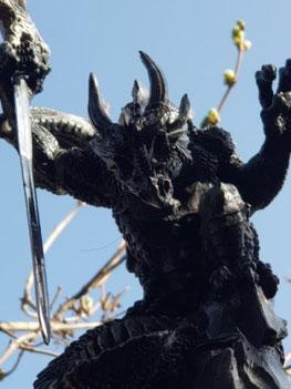 Symbol für die Angst und Panik, welche aus heiterem Himmel kommen kann. Eine Drachenfigur mit Schwert vor einem blauen Himmel.