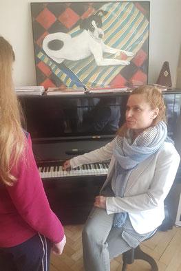 Iris Rufner sitzt am Klavier und erteilt einer Schülerin Gesangsunterricht.