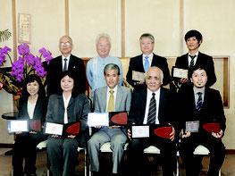 笑顔の受賞者、前列左端が米盛さん、4人目が譜久山さん、後列左から糸数正次認定委員会長、富川盛武副知事、新さん=28日午前、県庁副知事室