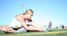 Sportlerin bei Dehnübungen