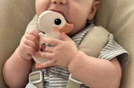 Baby sitzt im Hochstuhl mit einem Beissring aus Naturmaterialien