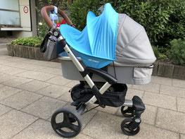 Grauer Kinderwagen steht auf der Straße bei Sonnenschein mit blauem Sonnensegel von ABC Design