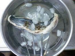 焼き目を付けたサワラを冷水で冷やす写真