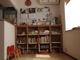 赤いイス、本棚、壁にホワイトボード、