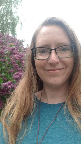 Stefanie Ihlenburg mit langen Haaren und Kette vor einem blühenden Busch