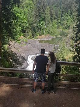 Zwei Personen vor Wasserfall