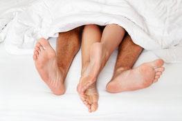 Unte reinen Bettdecke schauen die Füße einer Frau und eines Mannes heraus.