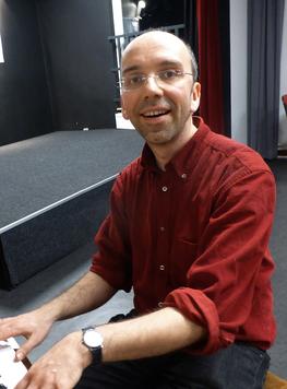 Klavierlehrer Valentin Dübbers sitzt am Klavier und guckt in die Kamera.