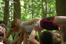 Titelbild der Kategorie Outdoor Teambuilding, Team hebt Frau waagerecht durch gespannte Seile