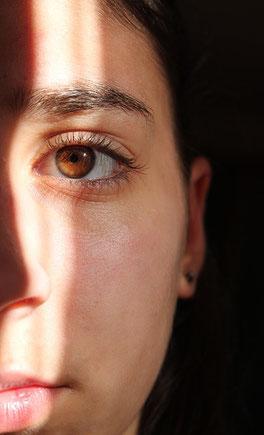 halbes senkrecht Gesicht im Bild, Frau mit braunen Augen und braunem Haar.