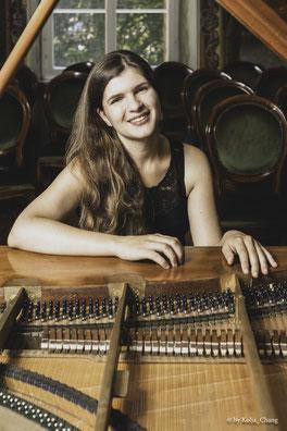 Klavierlehrerin Katja Poljakova sitzt an einem Holz-Piano