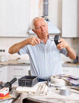 Ein Herr repariert ein Gerät.