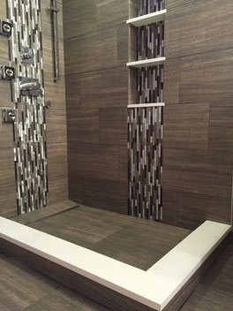 Wedi shower with line drain, a recessed shelf and a shower curb capped with white quartz. Tiled in darker brown linear 12x24 tiles with two vertical bands of linear mosaic: one behind the chrome shower head and controls and one behind the recessed shelf.