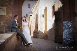 Die Braut steht mit einem glücklichen Lächeln und dem Brautstrauß in der Hand im Vordergrund. Im Hintergrund lehnt der Bräutigamm entspannt an einer Wand.
