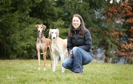 Frau in der Hocke sitzend, daneben stehend ihre zwei Hunde