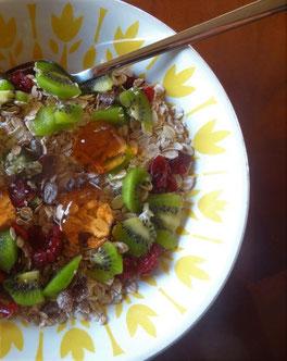 On voit une assiette avec du muesli, des morceaux de kiwi, des framboises, et de la gelée de coing