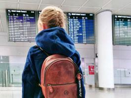 Kind wartet am Flughafen auf die Mama