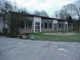 Schulgebäude mit Spielplatz