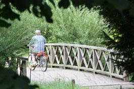 Radfahrer auf Holz-Brücke über einem Wasserarm Schlosspark Charlottenburg. Foto: Helga Karl
