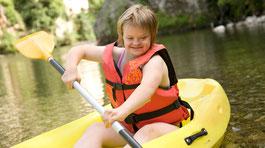 Ein Kind mit Down-Syndrom im Paddel-Boot © AdobeStock