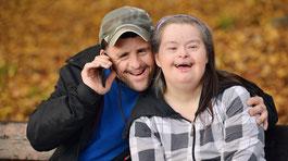 Ein Paar, beide mit Handicaps, sitzt auf einer Bank. Der Mann telefoniert. ©  AdobeStock