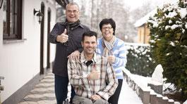 Ein junger Mann im Rollstuhl, hinter ihm Mutter und Vater. © AdobeStock