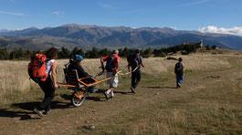 Eine Wandergruppe mit Trekking-Rollstuhl auf einem Pfad durch die Berge. ©  AdobeStock