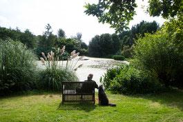 Frau auf Bank und Hund daneben sitzend, Blick auf einen See, Bonython Estate Gardens, Cornwall