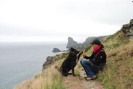 High Five von Frau und Hund auf dem South West Coast Path bei Tintagel, Cornwall