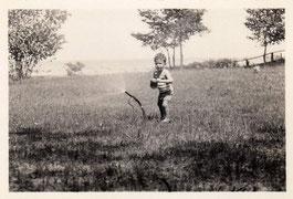 1925. Niño jugando con aspersor.